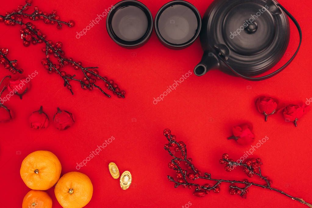 top view of chinese new year composition with tea and branches of berries on red