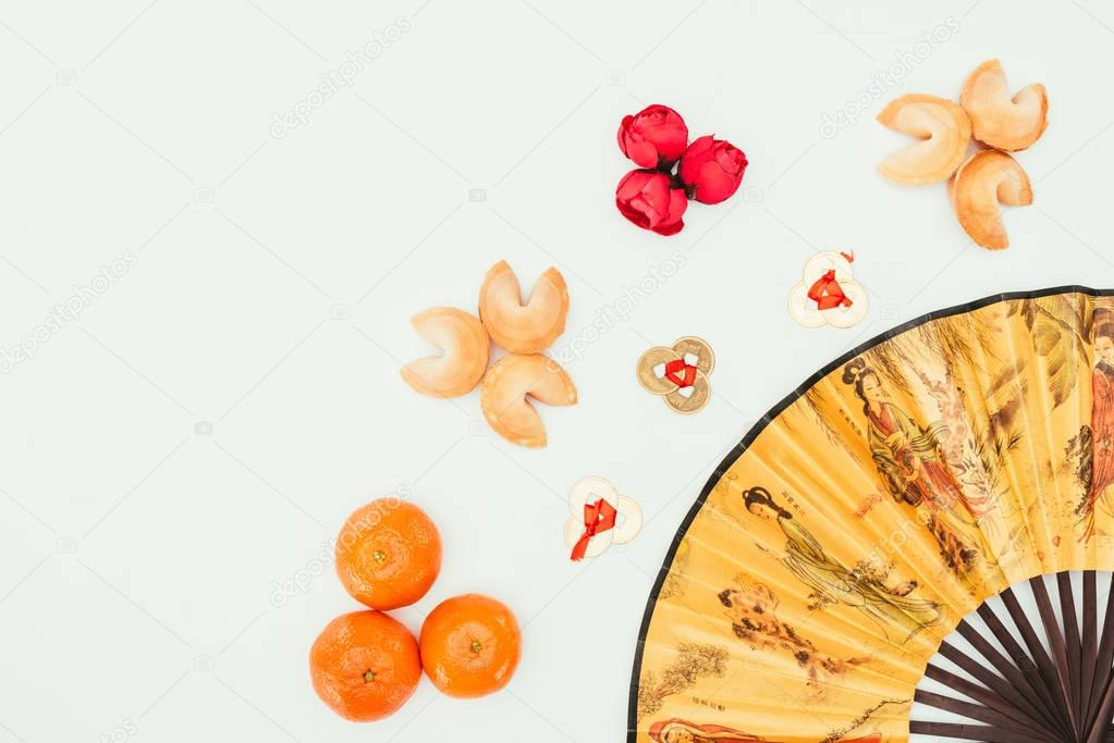 top view of chinese new year composition with handheld fan isolated on white
