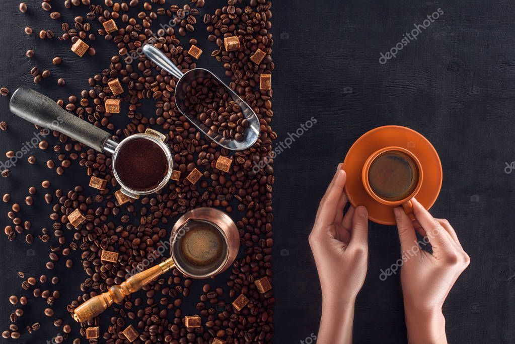 partial top view of person holding cup of coffee and roasted coffee beans with coffee pot, scoop and sugar