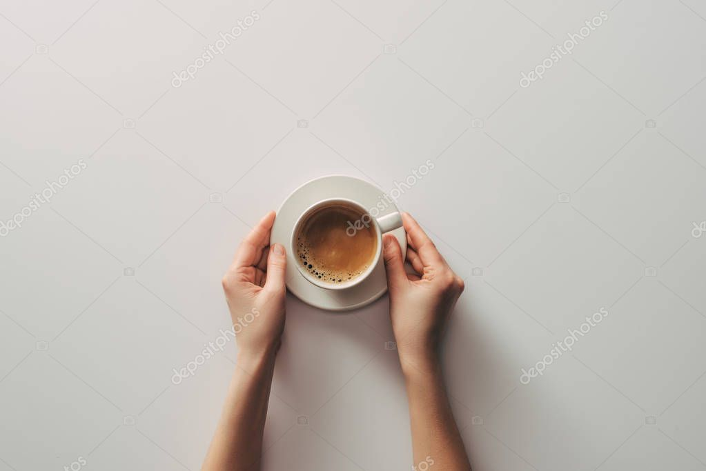 top view of female hands and cup of coffee with saucer on grey