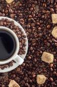 Detailní pohled šálek kávy, pražená kávová zrna a hnědého cukru na pytloviny