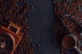 pohled shora pražená kávová zrna, mlýnek na kávu a lopatka na černém pozadí