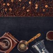 Fotografie pohled shora pražená kávová zrna, scoop, mlýnek na kávu, kávové konvice a kávovar na černém pozadí
