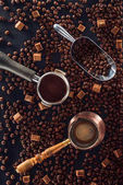 Photo top view of roasted coffee beans, scoop, coffee tamper, coffee pot and brown sugar on black