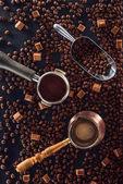 pohled shora pražená kávová zrna, scoop, pěch kávy, kávové konvice a hnědého cukru na černém pozadí