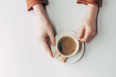 cropped view of human hands and cup of coffee on grey