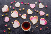 Fotografie st valentines day flat lay with cup of tea, glazed heart shaped cookies and decorative flowers on dark tabletop