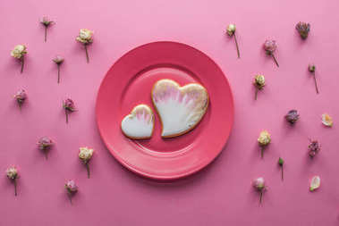 top view of sweet glazed cookies on plate with decorative flowers isolated on pink, st valentines day holiday concept