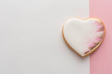 top view of glazed heart shaped cookie on pink surface
