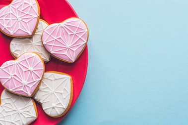 top view of glazed heart shaped cookies on pink plate isolated on blue