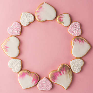 Flat lay with arrangement of glazed heart shaped cookies isolated on pink surface stock vector