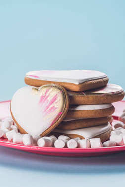 close up view of glazed cookies and marshmallow on pink plate isolated on blue