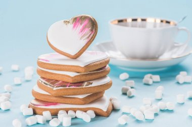 close up view of pile of glazed heart shaped cookies, marshmallow and cup isolated on blue, st valentines day concept
