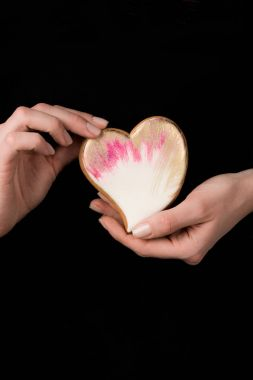 close up view of female hands with glazed heart shaped cookie isolated on black