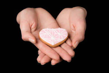 Close up view of female hands with glazed heart shaped cookie isolated on black stock vector