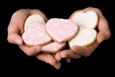 close up view of female hands with glazed heart shaped cookies isolated on black
