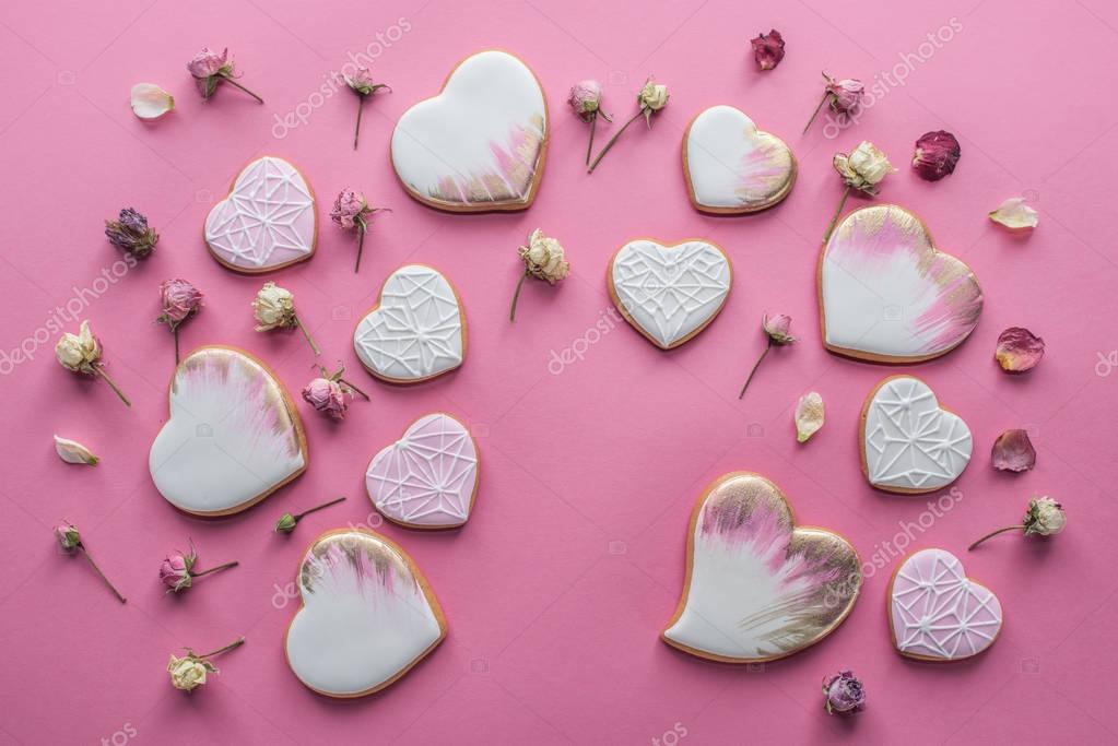 st valentines day arrangement of glazed heart shaped cookies and decorative flowers isolated on pink