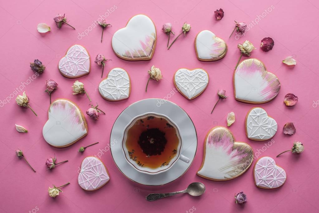 st valentines day arrangement of cup of tea, glazed heart shaped cookies and decorative flowers isolated on pink