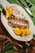 Draufsicht der Hering Fischstücke mit Zitrone und Zwiebel auf weißen Teller mit Getränke in Gläsern serviert