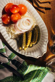 Photo Top view of sauerkraut served with pickled vegetables on white plate on wooden table with napkin