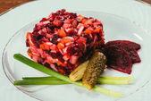 Vergrößerte Ansicht des Vinegret Salat serviert mit grünen Zwiebeln und Gewürzgurken auf weißen Teller