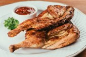 Photo grilled chicken laying on white plate with saucer on background