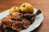 Photo fried duck pieces laying on plate with marinated apples over wooden table