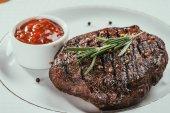 Datailní pohled grilovaný steak s pepřem, rozmarýnem a omáčkou na bílé plotně