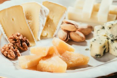 unpeeled pistachios and peeled walnuts laying on plate with cheese slices