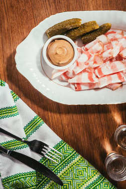 Top view of sliced bacon served with sauce and pickled cucumbers on plate served with drink on wooden table with napkin on wooden table stock vector