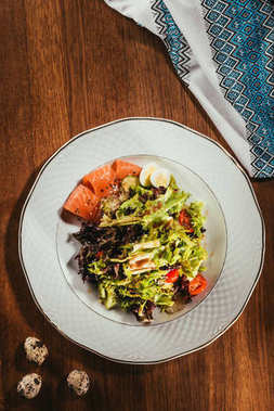 Top view of fresh salad with vegetables, eggs and salmon served on white plate with napkin on wooden table