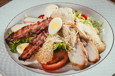 Close-up view of delicious salad with chicken meat, bacon, eggs and cheese dressing served on white plate