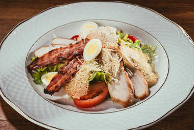 mixed leaf salad with ham slices and boiled eggs in plate over wooden surface
