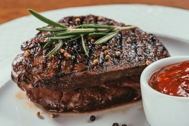 Close-up view of grilled steak with pepper, rosemary and sauce on white plate
