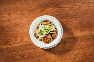 Top view of pickled mushrooms with onion on white plate on wooden table