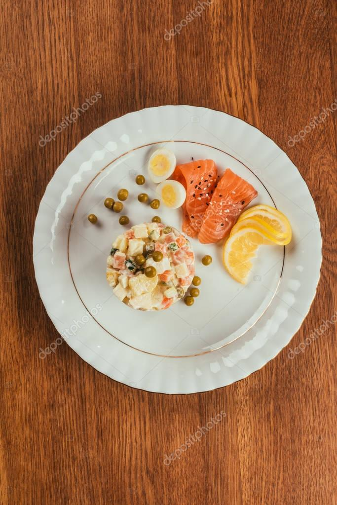 Russian salad on plate with scattered peas, boiled eggs and fish slices