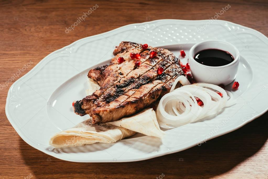 grilled steak on plate with onion rings and saucer with sauce over wooden surface