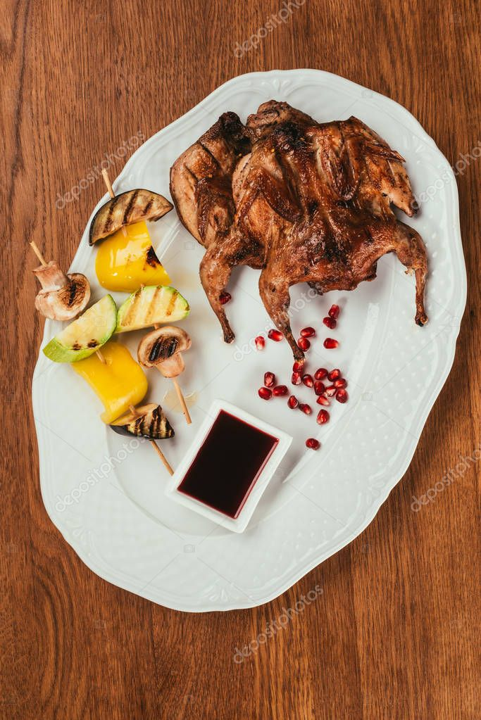 grilled chicken laying on plate with fried vegetables on skewer near saucer over wooden surface