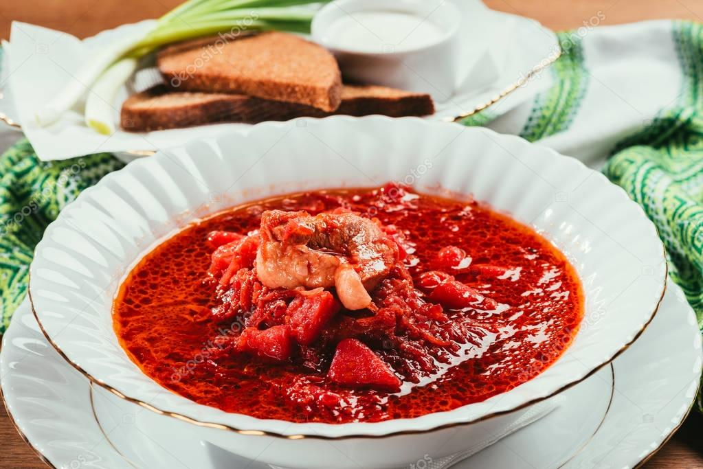 view of borsch soup with potato and meat in plate and green onions with bread and salt on background