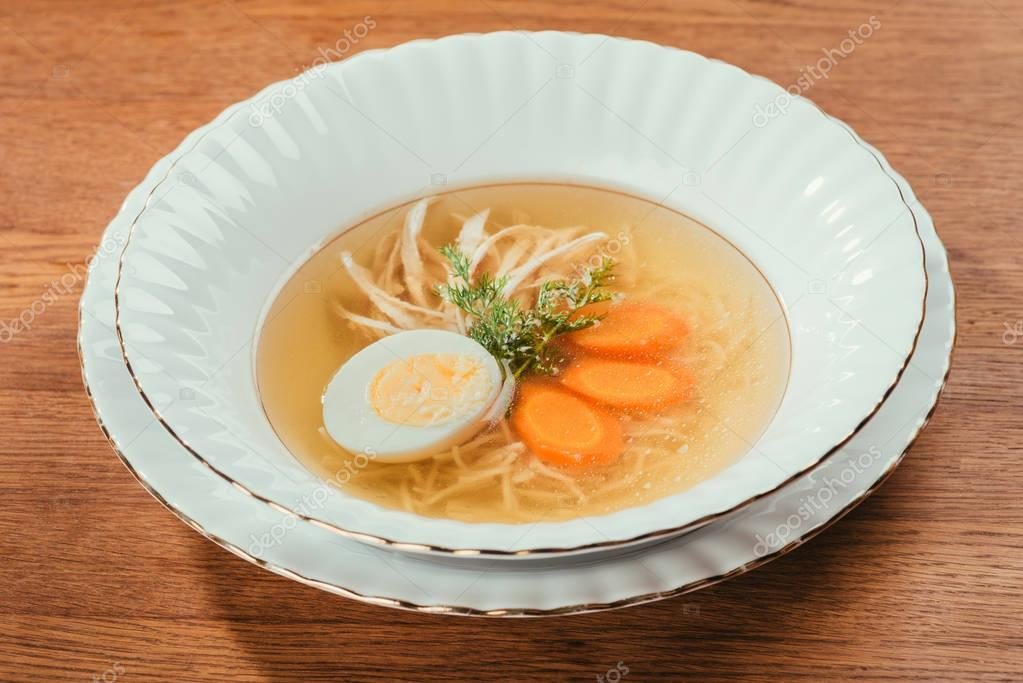 Chicken soup with vegetables and egg in white plate on wooden table