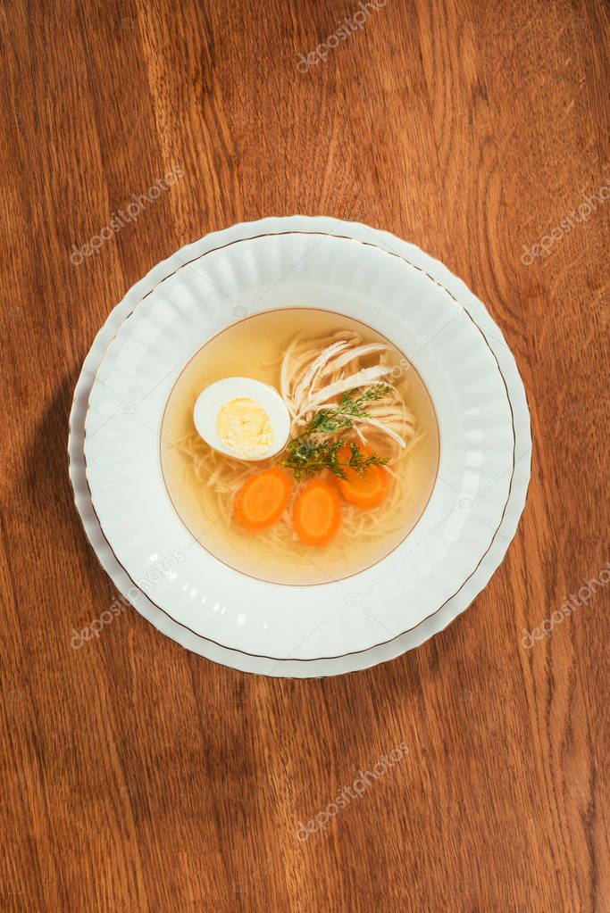 Top view of chicken soup with vegetables and egg in white plate on wooden table
