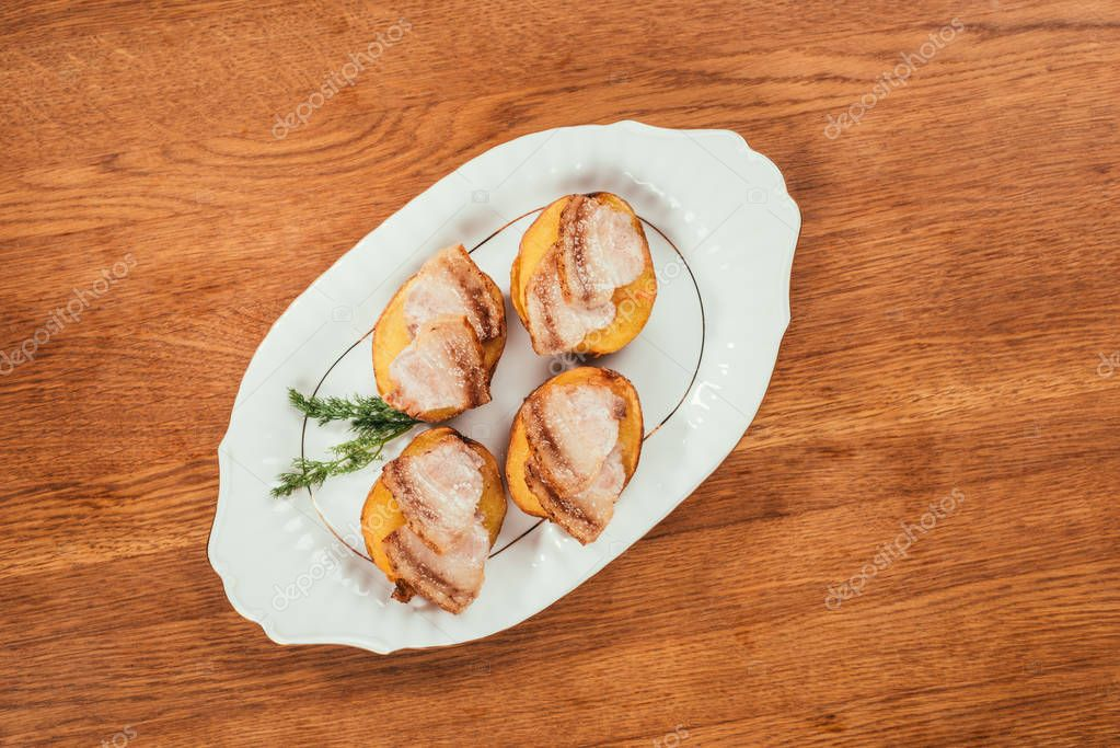baked potatos with ham slices on top laying on plate over wooden surface