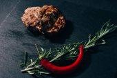 Detailní pohled grilované steaky s rozmarýnem a chili pepper na černém pozadí
