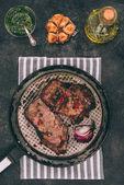 pohled shora lahodné pečené maso na pánev s kořením na černém pozadí