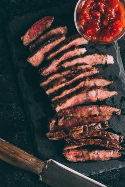 top view of delicious sliced grilled meat with sauce and knife on black slate board