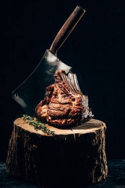 close-up view of delicious grilled ribs with meat knife and rosemary on wooden stump