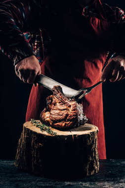 cropped shot of chef in apron holding fork and knife while slicing delicious grilled ribs on wooden stump