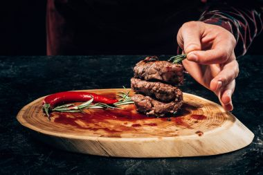 cropped shot of person putting rosemary on grilled steaks with chili pepper and sauce on wooden board