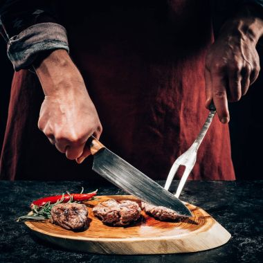 close-up partial view chef in apron with meat fork and knife slicing gourmet grilled steaks with rosemary and chili pepper on wooden board