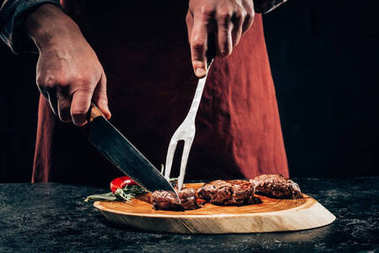 cropped shot of chef in apron with meat fork and knife slicing gourmet grilled steaks with rosemary and chili pepper on wooden board